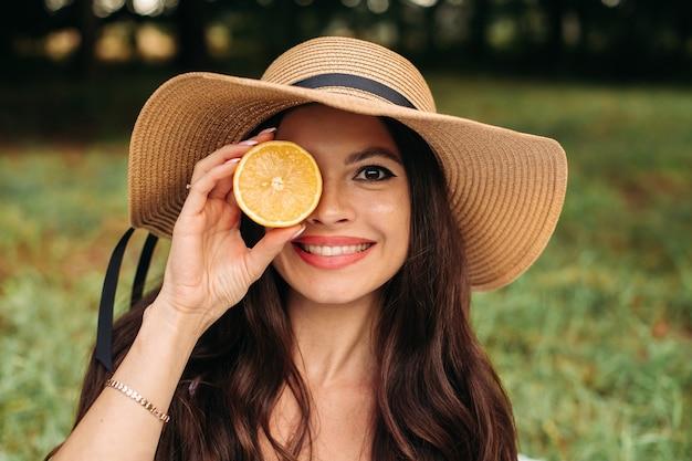 Stockfoto porträt des hübschen mädchens mit langen braunen haaren im stilvollen sommerhut, der halbe orange in der hand im park hält. mit glück in die kamera lächeln.
