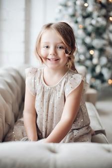 Stockfoto porträt des niedlichen kleinen mädchens im festlichen kleid mit reizendem hasen in ihren armen, die auf couch sitzen. unfokussierter verzierter weihnachtsbaum im hintergrund.