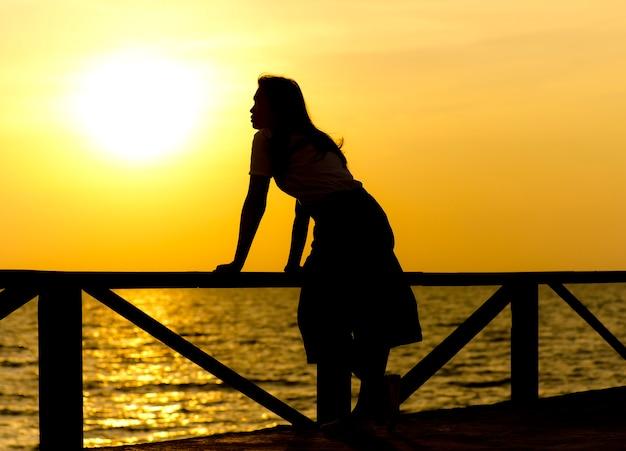 Stockfoto: profil einer aufpassenden sonne des frauenschattenbildes auf dem strand bei sonnenuntergang