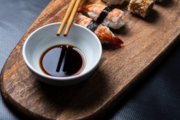 Stockfoto von essstäbchen, die in einer weißen schüssel mit sojasauce ruhen, umgeben von stücken von sushi auf einem schwarzen hintergrund.