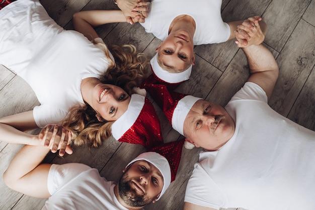 Stockfoto von vier erwachsenen leuten in den roten weihnachtsmützen, die hände halten, die auf dem boden liegen und lächeln.