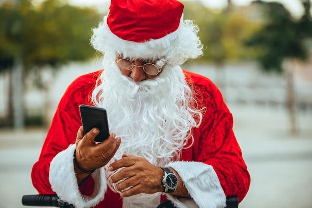 Stockfoto von weihnachtsmann, der mit einem handy mit einem park hinter unkonzentriert spricht. weihnachtszeit