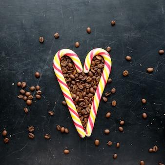 Stocksüßigkeiten in der herzform mit flacher ansicht der kaffeebohnen über schwarzen hintergrund