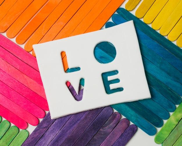 Stöcke in hellen lgbt-farben und liebeswort auf tablette