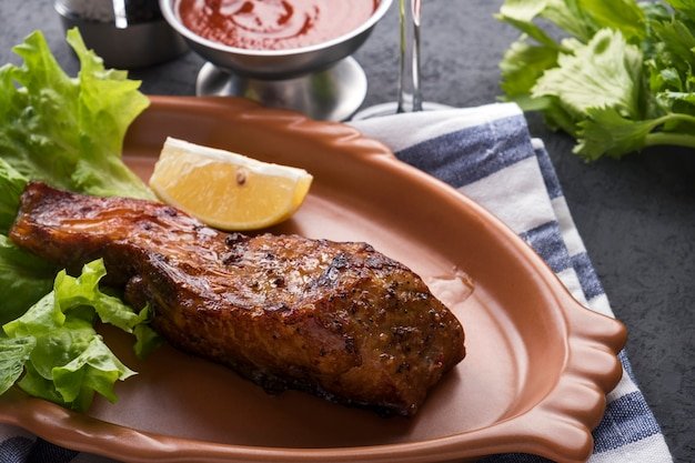 Stör auf einem grill mit zitrone und sauce.