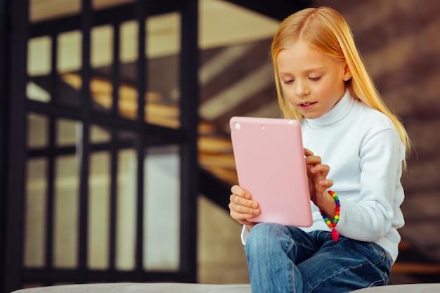 Stören sie mich nicht. nettes mädchen, das den kopf neigt, während es in den sozialen medien ist und nachrichten liest reading