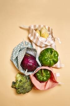 Stoff-baumwoll-einkaufstüten für lebensmittel mit gemüse. beiger hintergrund. kein plastik