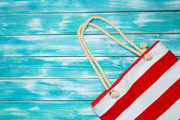 Stoff farbige strandtasche auf hellblauem holz
