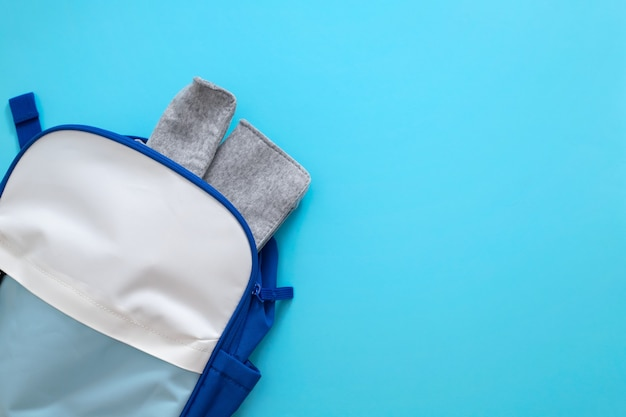 Stoff-federmäppchen und rucksack auf blauem hintergrund