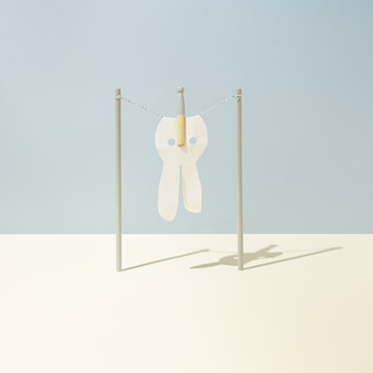 Stoff in form von osterhasen wird mit wäscheklammer auf wäscheleine auf pastellblauem und gelbem hintergrund befestigt. minimalistisches konzept. quadratisches layout