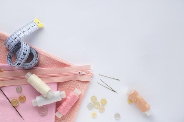 Stoff, nähgarne, nadeln, knöpfe und nähzentimeter.