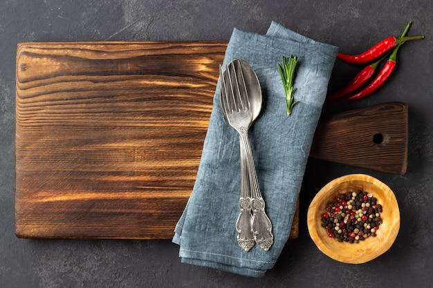 Stoff, pfefferkörner und besteck auf schneidebrett