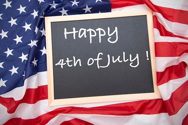 Stoff usa flagge mit tafel und text glücklicher 4. juli - unabhängigkeitstag