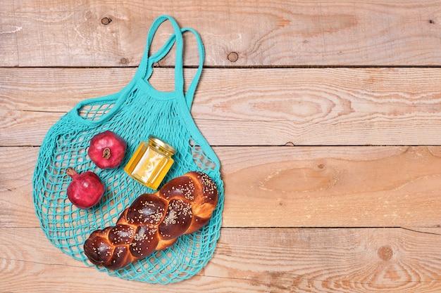 Stoffbeutel mit granatäpfeln, honig und challa, wiederverwendbares material für naturprodukte. null-abfall-konzept. chanukka. bewusstes konsumkonzept ohne plastikmüll. layout, holzhintergrund
