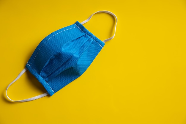 Stoffgesichtsmaske an gelber wand