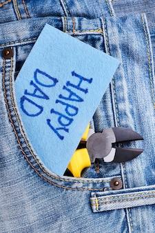 Stoffgrußkarte zum vatertag. zange und karte auf jeans. sende dem vater die besten wünsche.