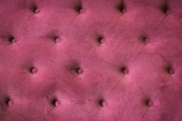 Stoffpolsterung auf der rückseite eines vintage-sofas burgunderrote hintergrundfarbe