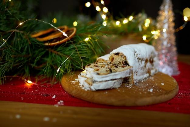 Stollen deutsches weihnachtsbrot, weihnachtsstollen auf holzhintergrund, traditionelles festliches gebäckdessert.