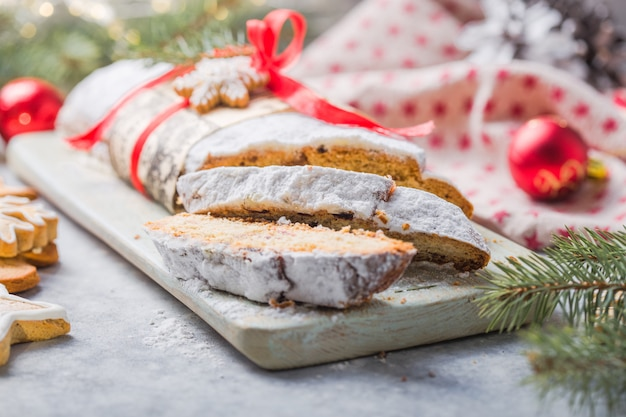 Stollen, ein traditioneller europäischer kuchen mit nüssen und kandierten früchten, wird mit puderzucker bestäubt und in stücke geschnitten