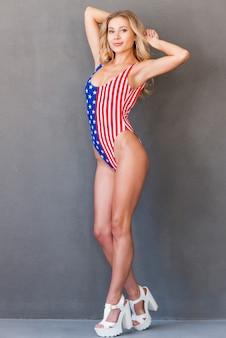 Stolz, amerikaner zu sein. volle länge der attraktiven jungen blonden haarfrau in der badebekleidung, die kamera beim stehen gegen grauen hintergrund betrachtet