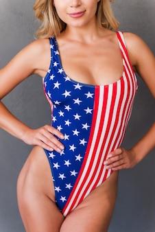 Stolz auf ihre perfekten kurven. abgeschnittenes bild einer attraktiven jungen blonden frau in badebekleidung, die hände an der hüfte hält, während sie vor grauem hintergrund steht