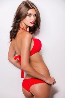 Stolz auf ihren perfekten körper. rückansicht einer attraktiven jungen frau mit braunen haaren im roten bikini, die vor weißem hintergrund posiert