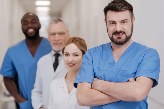 Stolz auf mein internationales team. hübscher, selbstbewusster, kompetenter praktiker, der die verantwortung im krankenhaus genießt und mit verschränkten armen steht, während er lächelt