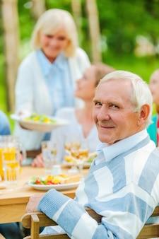 Stolz, eine große familie zu haben. glückliche familie, die draußen am esstisch sitzt, während ein älterer mann über die schulter schaut und lächelt