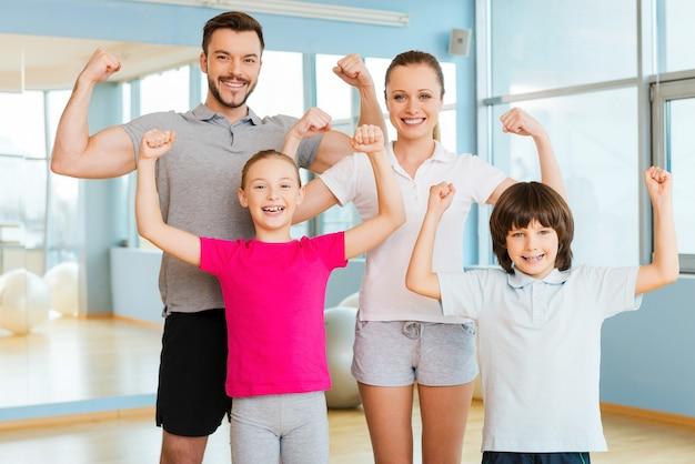Stolz, stark und gesund zu sein. glückliche sportliche familie, die ihren bizeps zeigt und lächelt, während sie im sportverein nahe beieinander steht
