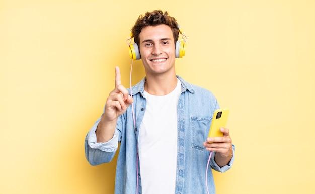 Stolz und selbstbewusst lächeln, die nummer eins triumphierend posieren lassen und sich wie ein anführer fühlen. kopfhörer- und smartphone-konzept