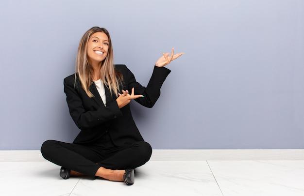 Stolz und selbstbewusst lächeln, sich glücklich und zufrieden fühlen und ein konzept auf dem kopierplatz zeigen
