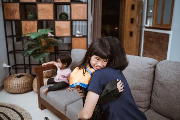 Stolze asiatische mutter umarmt ihre tochter während des grundschulabschlusstages