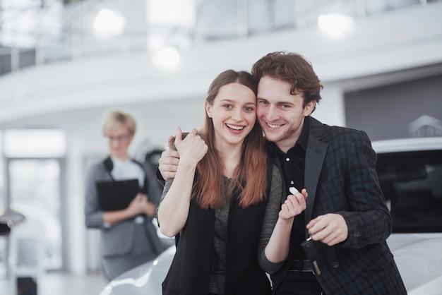 Stolze besitzer. schönes junges glückliches paar, welches die stellung nahe ihrem eben gekauften auto lächelt umarmt, freudig autoschlüssel zeigend
