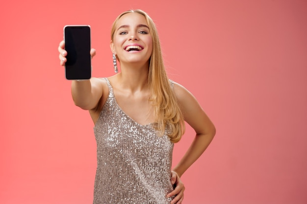 Stolze, fröhliche, charmante, fröhliche, blonde europäische frau in stilvollem silber glänzendem kleid halten hand taille selbstbewusst verlängern arm mit smartphone-display präsentieren tolles neues app-gerät, roter hintergrund.