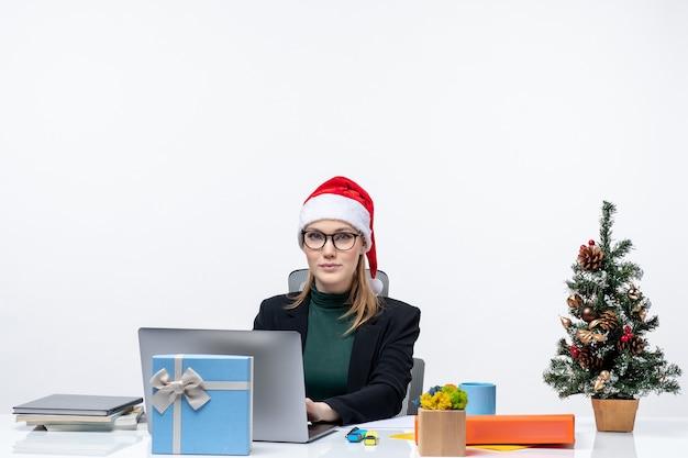 Stolze glückliche geschäftsfrau mit einem weihnachtsmannhut, der an einem tisch mit einem weihnachtsbaum und einem geschenk darauf sitzt und ihre mails auf weißem hintergrund überprüft