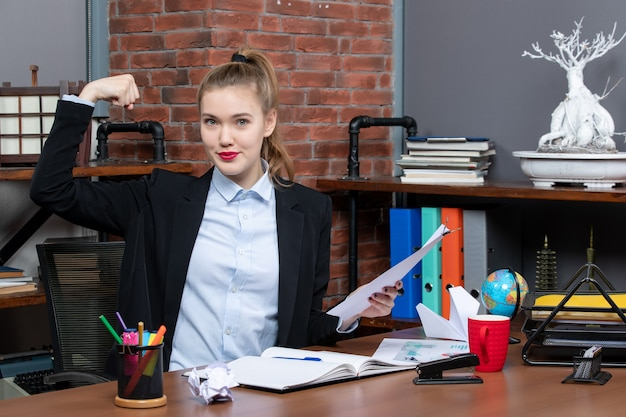 Stolze junge dame, die an einem tisch sitzt und das dokument hält, das ihre stärke im büro zeigt