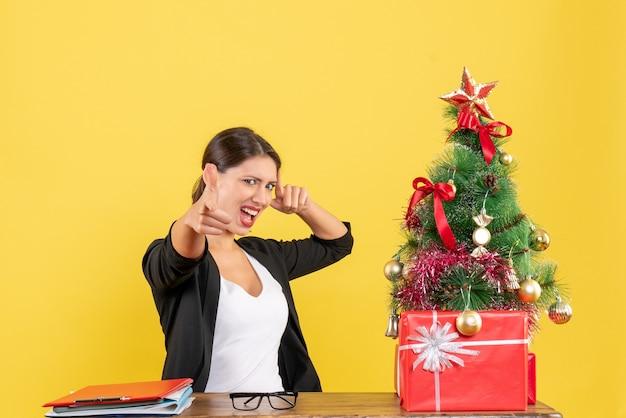 Stolze junge frau im anzug mit geschmücktem weihnachtsbaum im büro auf gelb