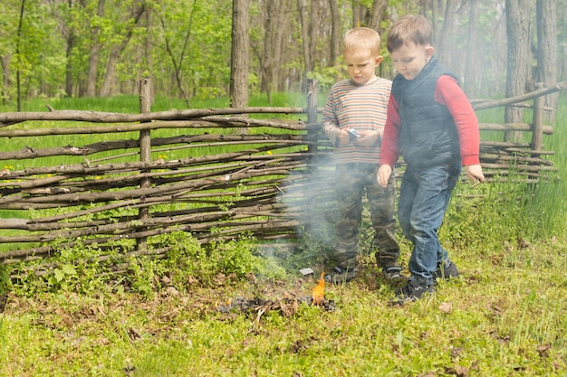 Stolze kleine jungs stehen und beobachten ein brennendes feuer