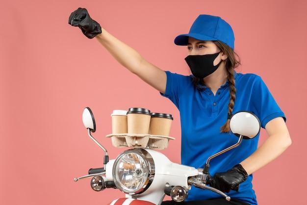 Stolze kurierin mit schwarzer medizinischer maske und handschuhen, die bestellungen auf pfirsichhintergrund liefert