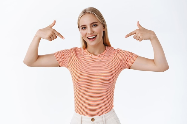 Stolze, prahlerisch gutaussehende, stylische junge frau mit blonden haaren, tätowierungen, stehendem gestreiftem t-shirt, die sich als prahlend zeigt, frech lächelt, als werbeträger angibt, weißer hintergrund