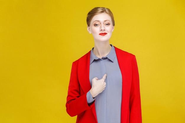 Stolze rothaarige geschäftsfrau im roten anzug, die auf sich selbst zeigt