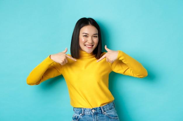 Stolze und glückliche asiatische frau, die zufrieden lächelt, auf sich selbst zeigt und wie ein profi in die kamera aussieht, in freizeitkleidung auf blauem hintergrund steht