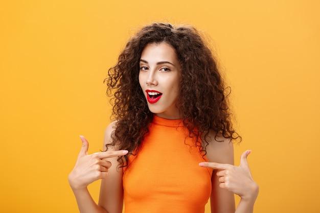 Stolze und zufriedene coole urbane frau mit rotem lippenstift und lockiger frisur, die mit selbstbewusstem ausdruck auf sich selbst zeigt und mit fähigkeiten und leistungen auf orangefarbenem hintergrund prahlt.