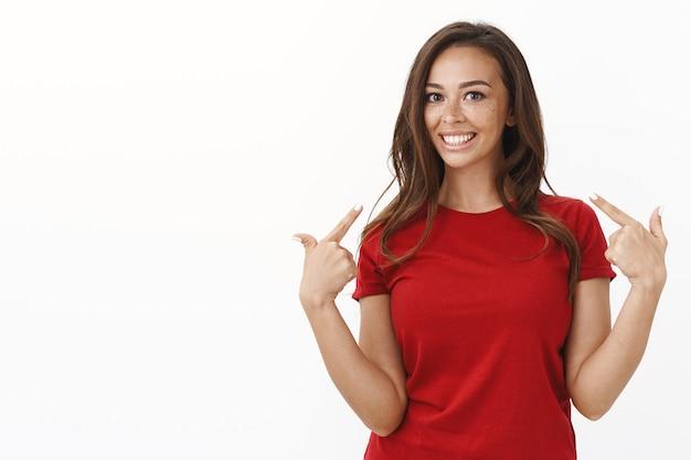 Stolze und zufriedene, gutaussehende frau, die ihr strahlend weißes lächeln zeigt, sich selbst zeigt und entzückt grinst, begeistert an der veranstaltung teilnimmt, sich freiwillig meldet, eigene kandidatur vorschlagen