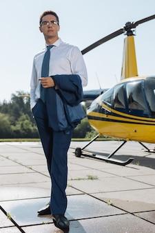 Stolzer besitzer. hübscher junger ceo in einem anzug, der eine jacke über dem arm hält und an seinem eigenen hubschrauberlandeplatz für die kamera posiert
