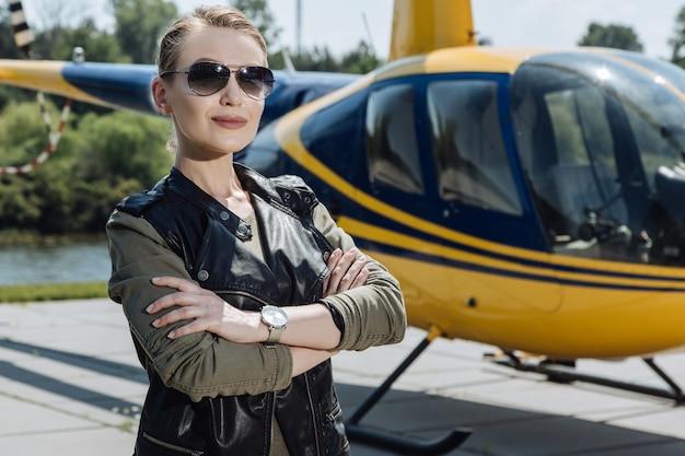 Stolzer hubschrauberbesitzer. wunderschöne pilotin posiert an einem hubschrauberlandeplatz in der nähe eines hubschraubers, während sie die arme vor der brust verschränkt