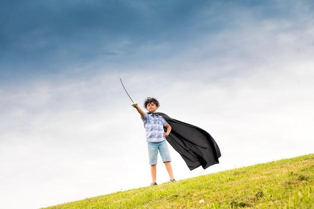 Stolzer junge, der den superhelden spielt