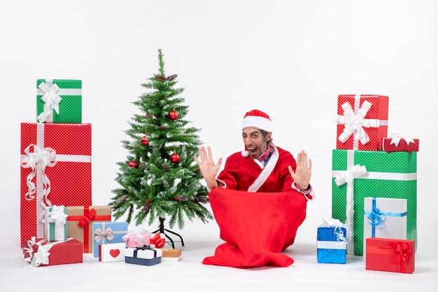 Stolzer junger erwachsener verkleidet als weihnachtsmann mit geschenken und geschmücktem weihnachtsbaum, der auf dem boden auf weißem hintergrund sitzt