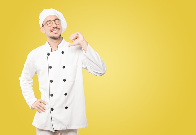 Stolzer junger koch, der eine hochmütige geste macht