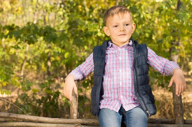 Stolzer kleiner junge, der draußen auf einem holzzaun im wald sitzt, seine hände auf zwei pfosten ruht und mit einem lächeln nach vorne schaut, mit exemplar copy